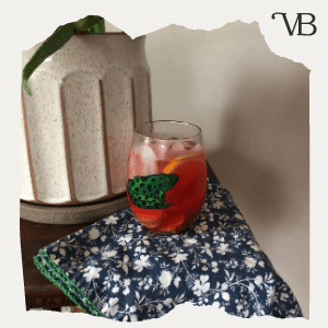 Blueberry Summer Mocktail: A photo of a mocktail that is a blue color sitting on a table with an aloe plant.