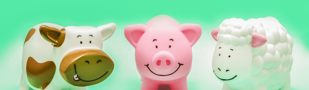 a toy cow, a toy pig, and a toy sheep standing next to each other with a green background