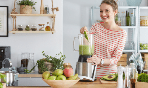 woman adding food to a blender to make a meal for a vegan bariatric pureed diet