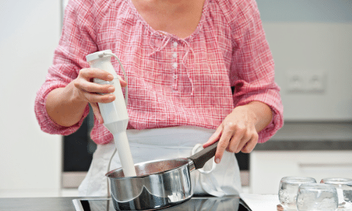 woman wearing a pink shirt using immersion blender to blend contents of a small sauce pan