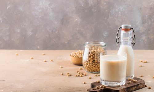 bottle and cup of soy milk sitting next to dry soy beans